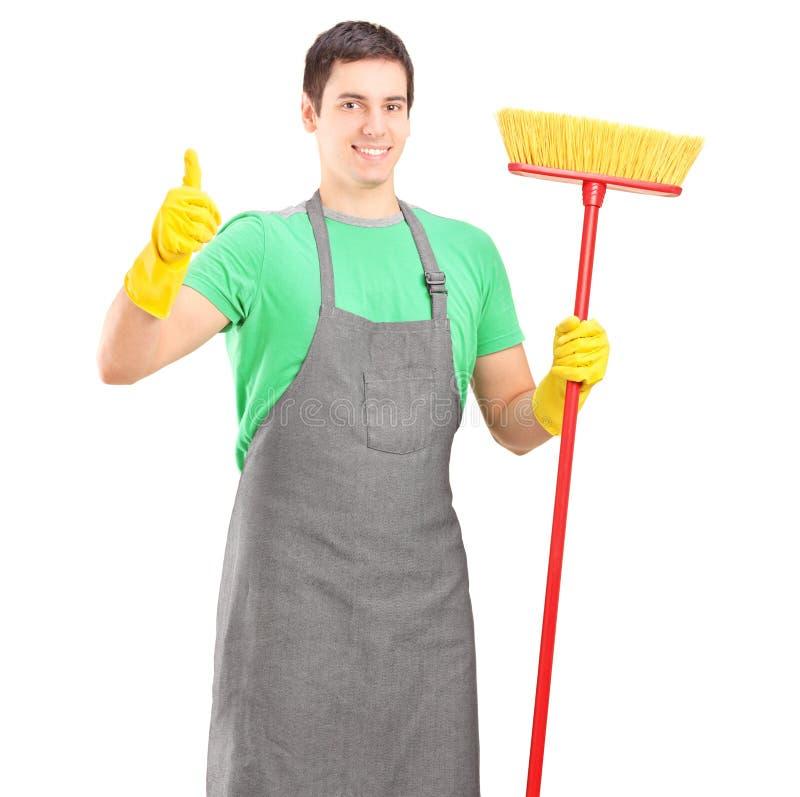 Nettoyeur posant avec le balai et renonçant au pouce photos stock