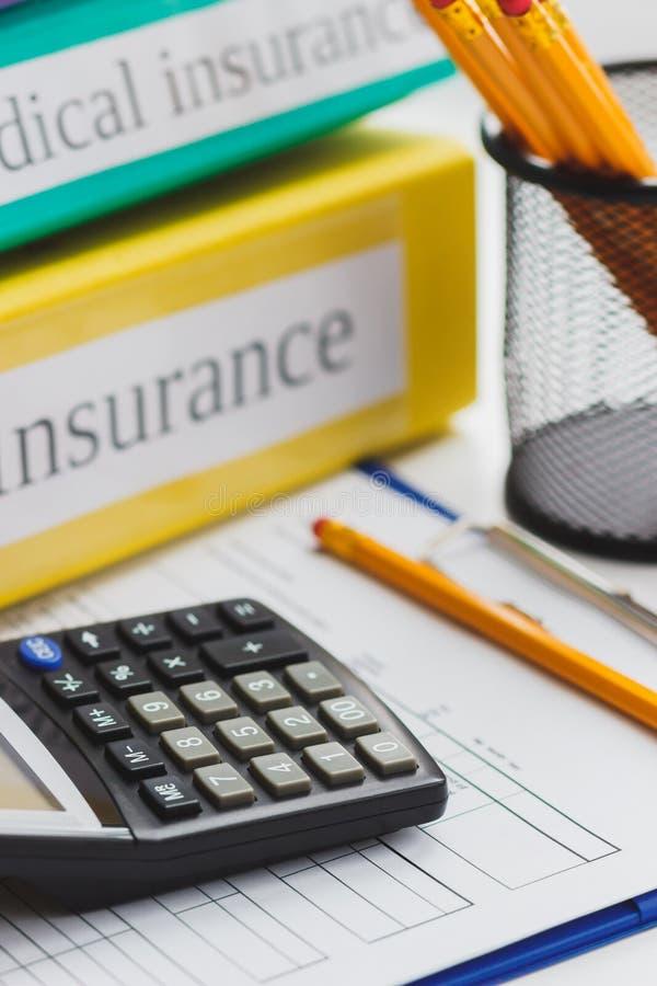 Nettoyez la forme d'assurance, calculatrice, dossiers et des crayons photographie stock