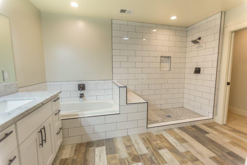 Nettoyez la salle de bains spacieuse de chambre à coucher principale avec des planchers de douche et de baquet et en bois en San  photographie stock