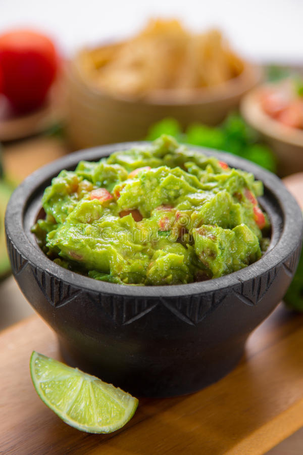 Nettoyez le tir vertical d'un bol frais de puces de guacamole et de tortilla de style de restaurant image libre de droits