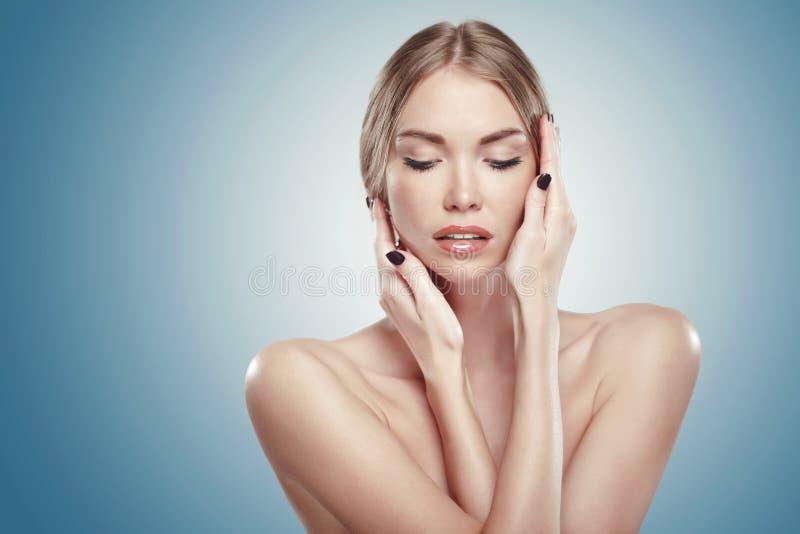 Nettoyez le visage de la belle fille de l'adolescence touchant ses joues photographie stock