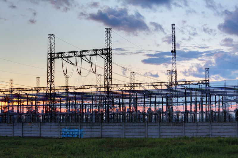 Netwerk bij transformatorpost in zonsopgang, hoogspanning stock foto