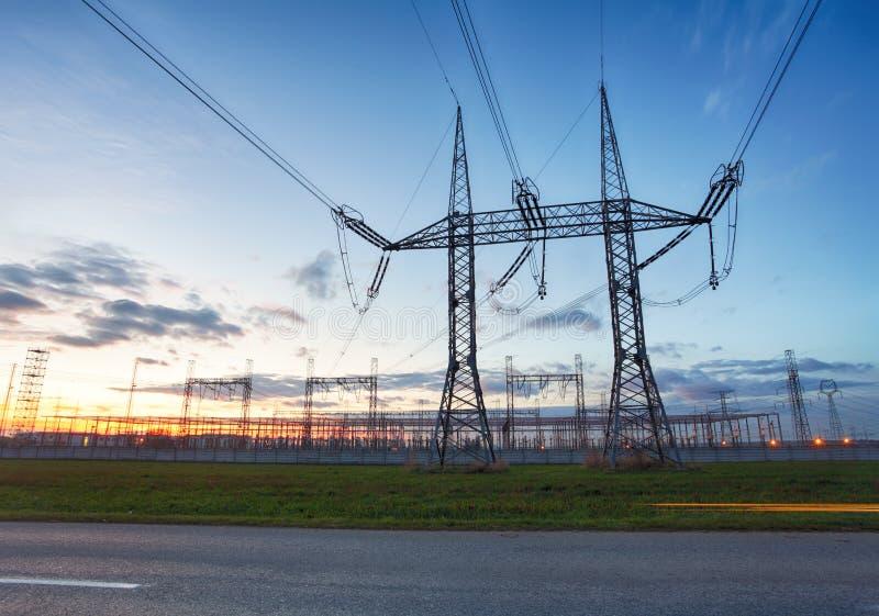 Netwerk bij transformatorpost in zonsopgang, hoogspanning stock afbeeldingen