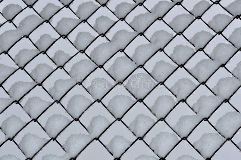 Netwerkomheining in sneeuw wordt behandeld die stock afbeeldingen