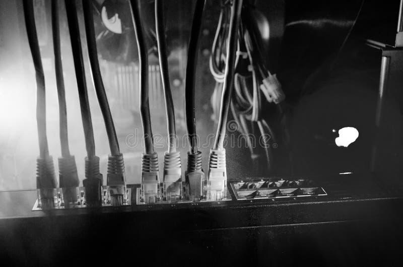 Netwerkschakelaar en ethernet kabels, symbool van globale mededelingen Gekleurde netwerkkabels op donkere achtergrond met lichten royalty-vrije stock foto's