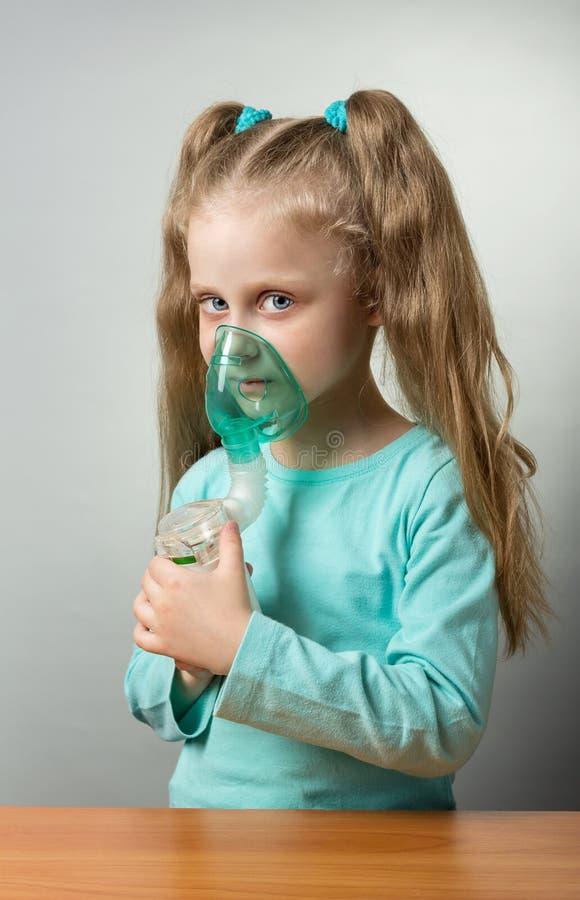 Netwerkverstuiver met kindmasker in handen van ziek kind, op grijs stock foto's