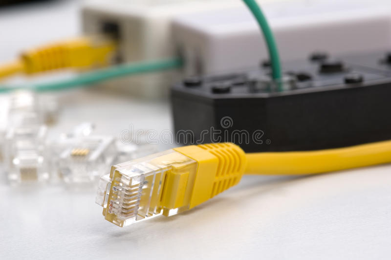 Network cable. Yellow rj-45 network cable in focus and crimping tool, plugs and sockets in background