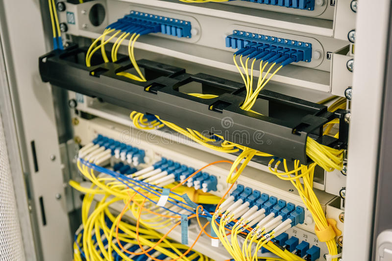 Network cables connected to switches ports in datacenter cupboard, web or cellular server hardware equipment. Information technology internet concept stock photography