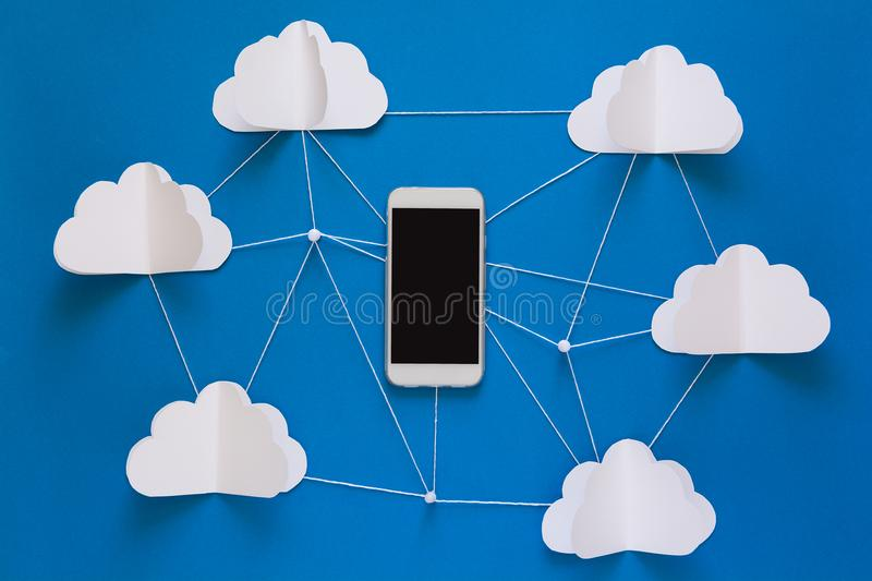 Data communications and cloud computing network concept. Smart phone flying on paper cloud. royalty free stock photography