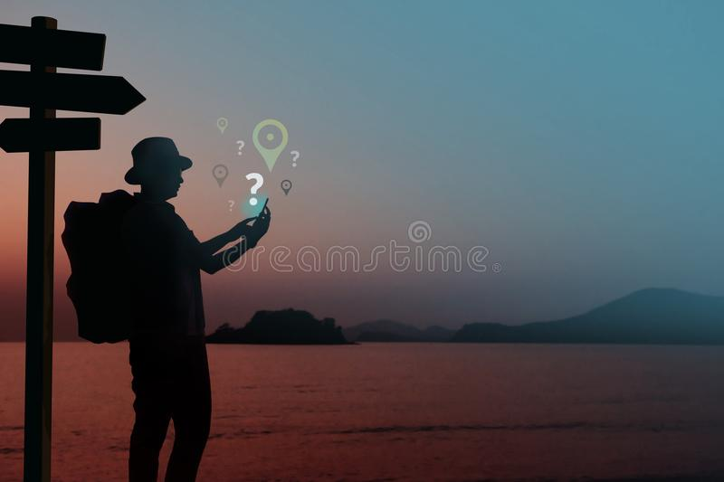 Network Connection Lost for Travel Concept, Silhouette of Backpacker using Smart Phone in unknown place with Question and stock image