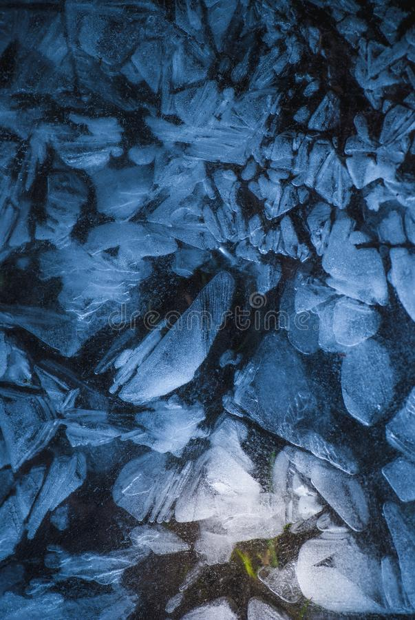 Network of cracks in thick solid frozen layer of ice with shining light and green grass in the deep royalty free stock photo