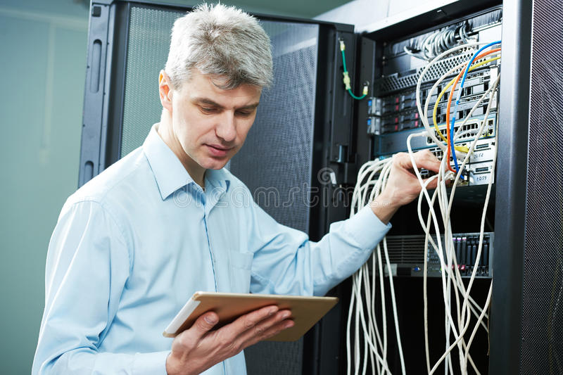 Network engineer administrator in server room. Network engineer admin or server administrator technician worker at data center room stock photo