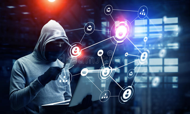 Network security and privacy crime. Mixed media. Computer hacker in hoodie and mask stealing data from laptop. Mixed media royalty free stock photo