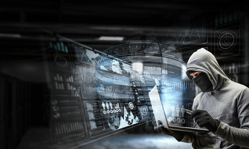 Network security and privacy crime. Mixed media. Computer hacker in hoodie and mask stealing data from laptop. Mixed media royalty free stock photography