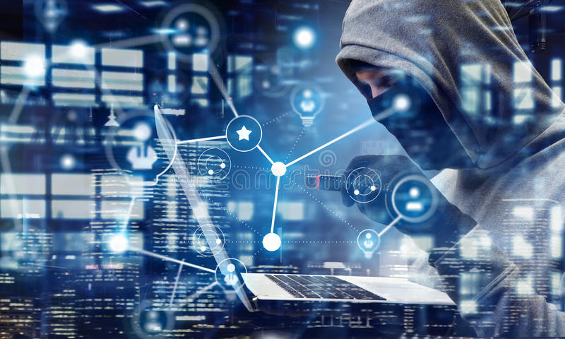 Network security and privacy crime. Mixed media. Computer hacker in hoodie and mask stealing data from laptop. Mixed media stock images