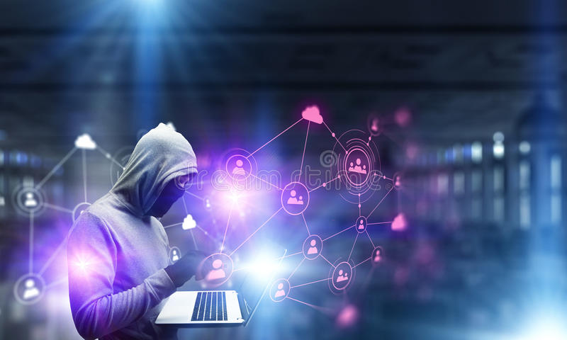 Network security and privacy crime. Mixed media. Computer hacker in hoodie and mask stealing data from laptop. Mixed media stock photo