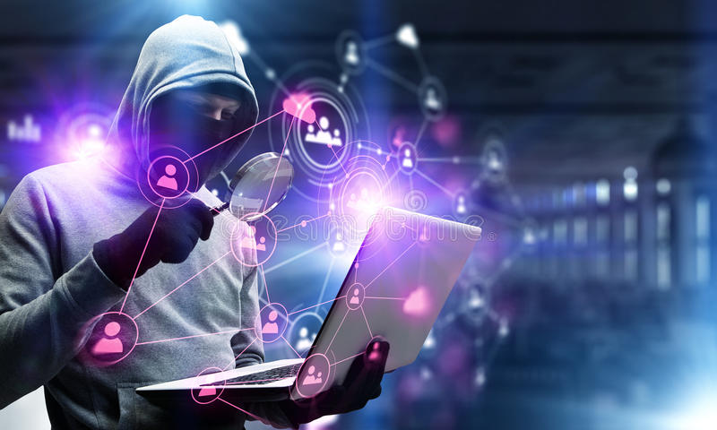 Network security and privacy crime. Mixed media. Computer hacker in hoodie and mask stealing data from laptop. Mixed media stock photography