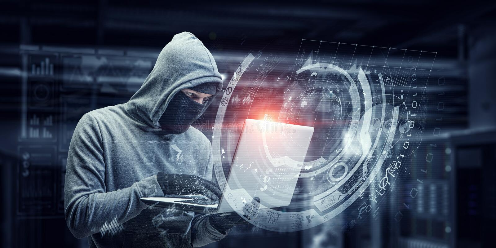 Network security and privacy crime. Mixed media. Computer hacker in hoodie and mask stealing data from laptop. Mixed media royalty free stock image
