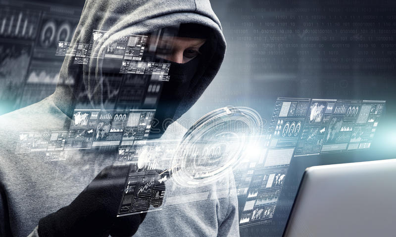 Network security and privacy crime. Mixed media . Mixed media. Computer hacker in hoodie and mask stealing data from laptop. Mixed media royalty free stock images
