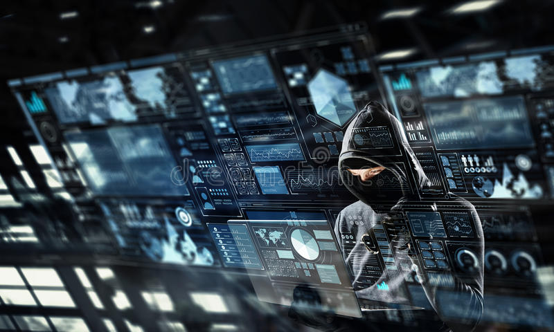 Network security and privacy crime. Mixed media . Mixed media. Computer hacker in hoodie and mask stealing data from laptop. Mixed media royalty free stock image