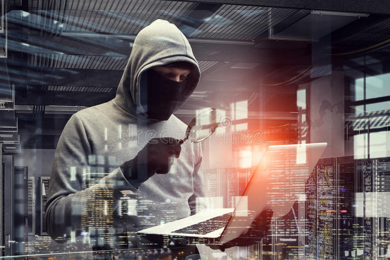 Network security and privacy crime. Mixed media . Mixed media. Computer hacker in hoodie and mask stealing data from laptop. Mixed media stock images