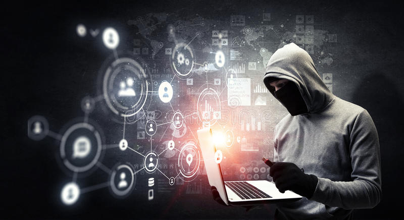 Network security and privacy crime. Mixed media . Mixed media. Computer hacker in hoodie and mask stealing data from laptop. Mixed media stock photo