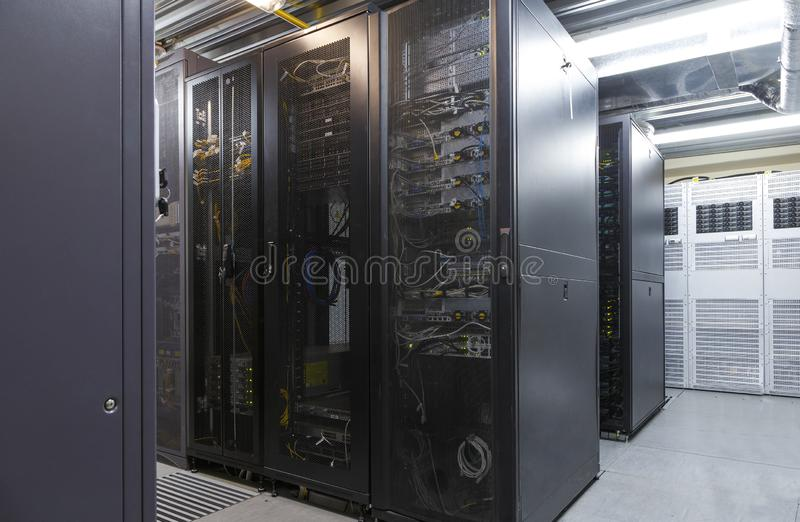 Network server room with parallel rows of mainframe. Corridor in big working data center full of rack servers and supercomputers. Networking and technology royalty free stock image