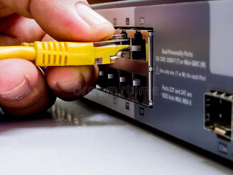 Network switch and ethernet cables,Data Center Concept To communicatation,Information technology,Man connecting network cable to stock photo