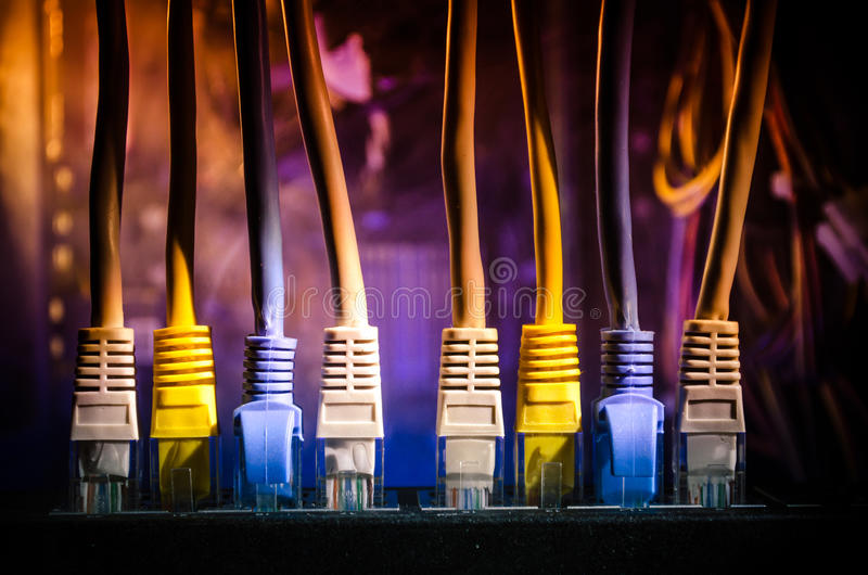 Network switch and ethernet cables, symbol of global communications. Colored network cables on dark background with lights and smo royalty free stock images