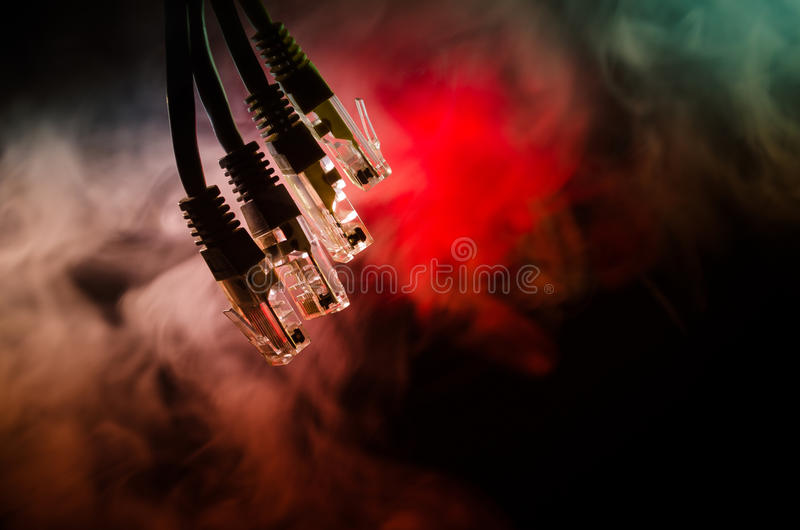 Network switch and ethernet cables, symbol of global communications. Colored network cables on dark background with lights and smo stock photos