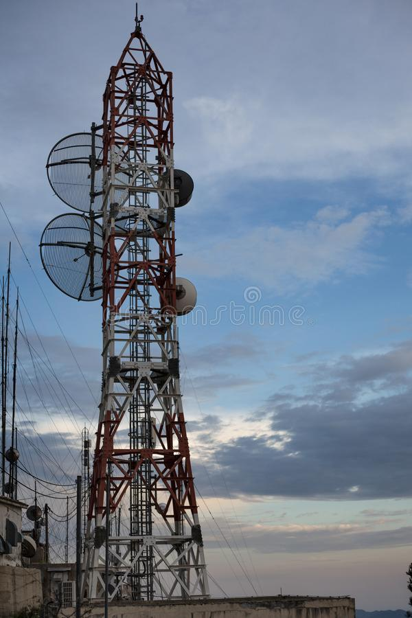 An network tower standing tall near the cliff besides a sandy beach. Dozens of wire connected to each transmission to give supply stock images