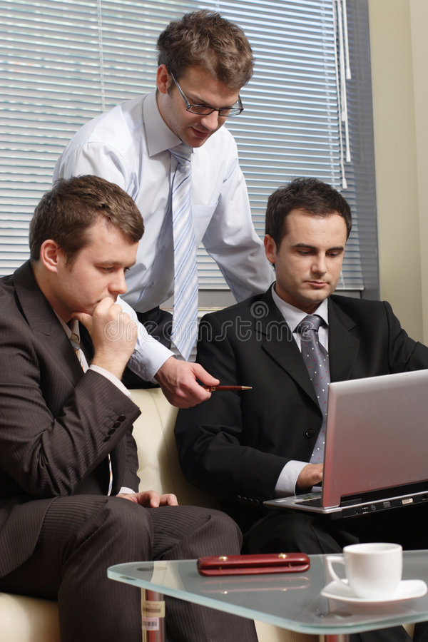 Networking. Three young business men working together with laptop in the office stock image
