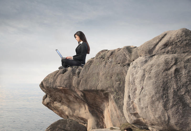 Networking. Businesswoman sitting on a rock and using a laptop