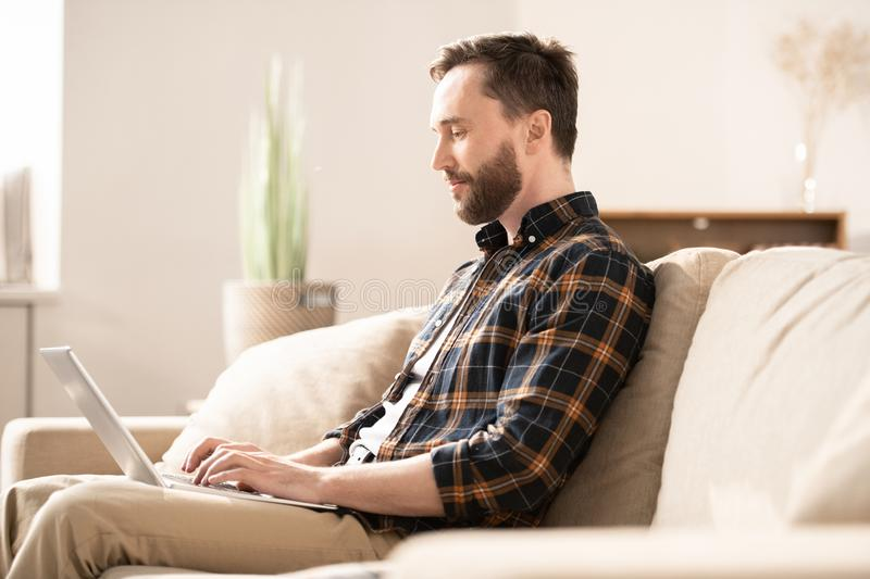 Networking on couch. Contemporary young home office employee in casual shirt and jeans sitting on couch in front of laptop display stock image