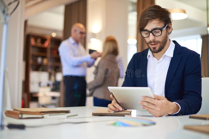 Networking. Handsome businessman in casual networking on background of his partners royalty free stock photo