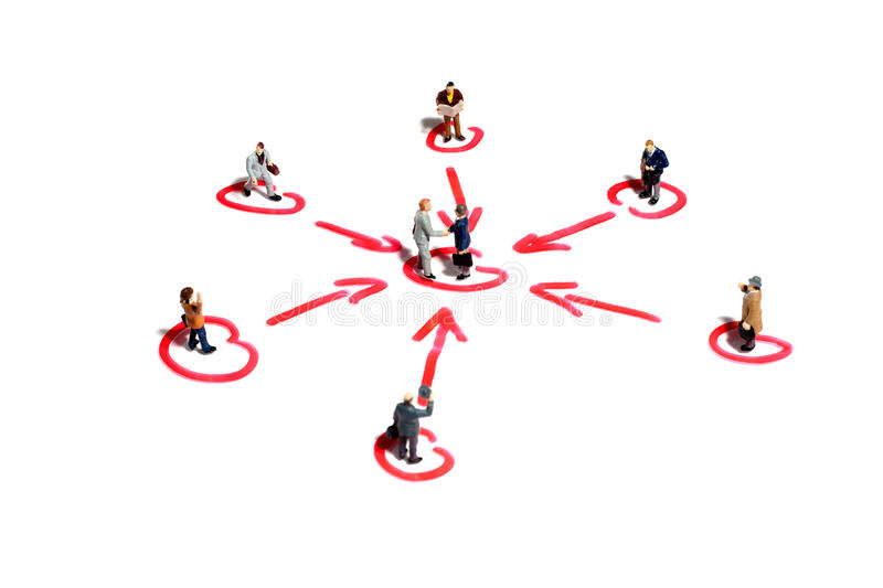 Networking and support in business. Two tiny miniature businessmen shake hands in the centre of a networking web surrounded by linked colleagues offering support stock photos