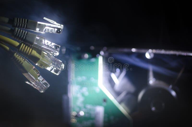 Netzschalter und Ethernet-Kabel, Symbol von globalen Kommunikationen Farbiges Netz verkabelt auf dunklem Hintergrund mit Lichtern stockbilder