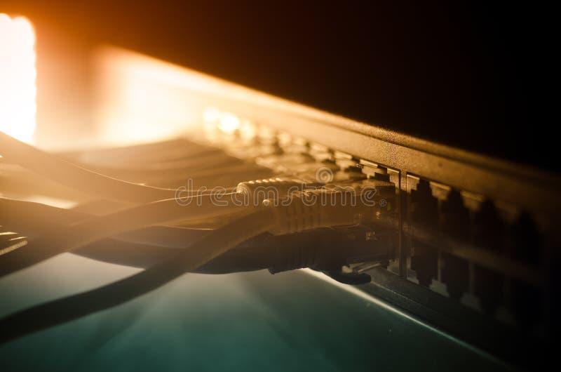 Netzschalter und Ethernet-Kabel, Symbol von globalen Kommunikationen Farbiges Netz verkabelt auf dunklem Hintergrund mit Lichtern stockbild