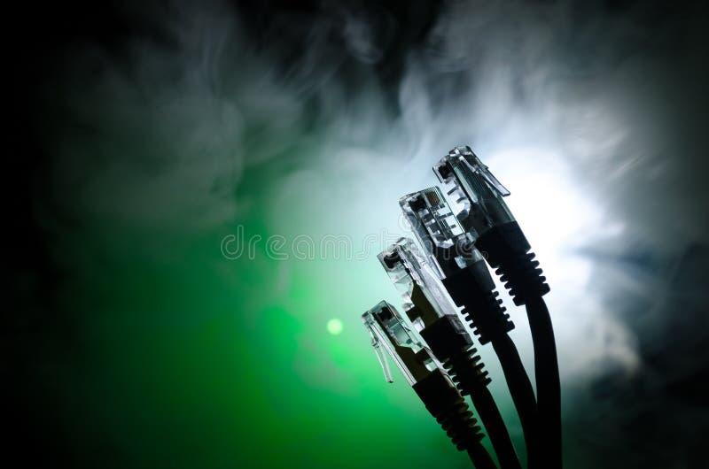 Netzschalter und Ethernet-Kabel, Symbol von globalen Kommunikationen Farbiges Netz verkabelt auf dunklem Hintergrund mit Lichtern stockfotografie