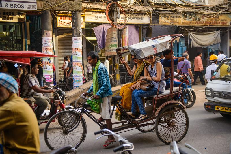 Neu-Delhi, Indien - 16. April 2016: Rikschareiter transportiert Passagier am 16. April 2016 in Neu-Delhi, Indien Fahrradrikschas lizenzfreies stockfoto