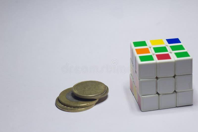 Neu-Delhi, Indien - 10. November 2019 Münzen und Rubik's Würfel auf weißem Hintergrund mit Leerzeichen lizenzfreies stockfoto