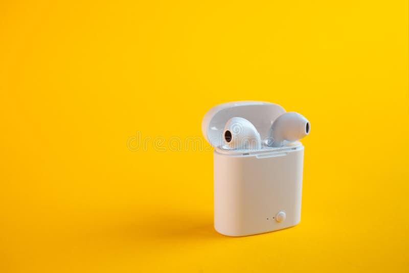 Neue drahtlose Kopfh?rer im Aufladungskasten stockfotos