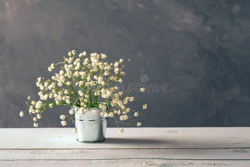 Neue Frühlingsblumenanordnung im metallischen Eimer auf hölzernem Schreibtisch stockbilder