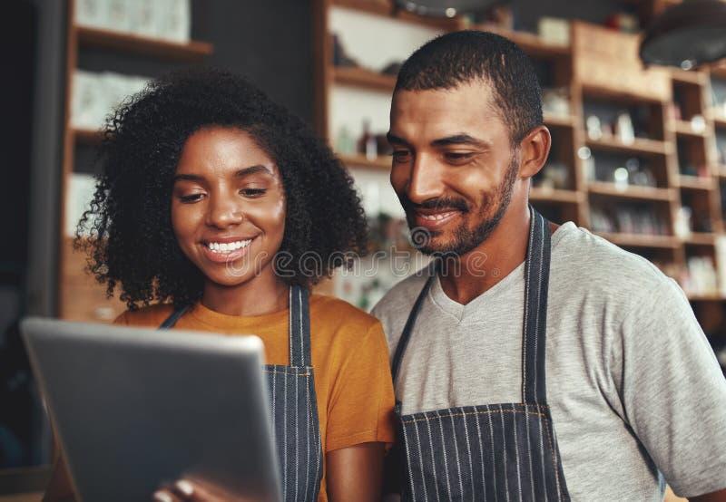 Neue Geschäftseigentümer, die Tablette im Café verwenden lizenzfreie stockfotos