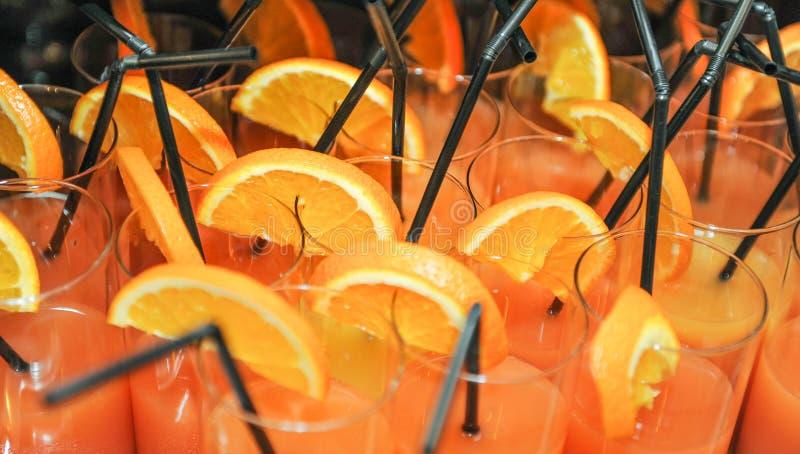 Neue Getränke mit orange Scheiben und Strohen, Abschluss oben Orangensaft in den Gläsern mit Strohen, bereiten vor getrunken zu w stockfotos