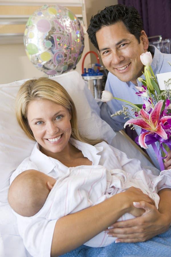 Neue Mutter mit Schätzchen und Ehemann im Krankenhaus lizenzfreie stockbilder