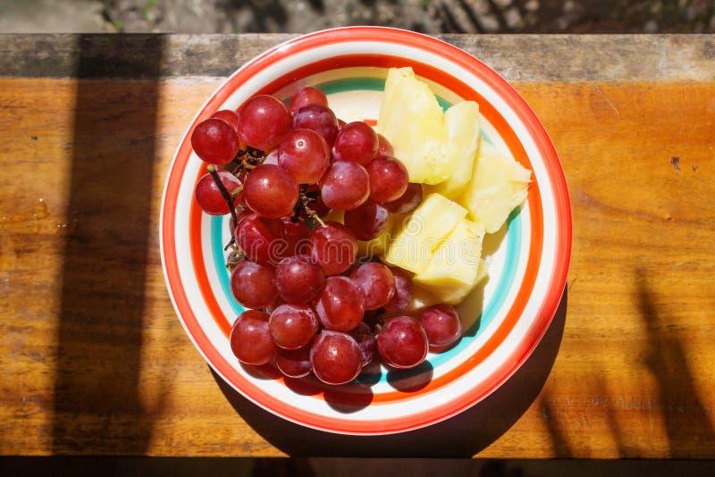 Neue rote Trauben und Ananasscheiben auf farbiger Platte, Guatemala stockbild