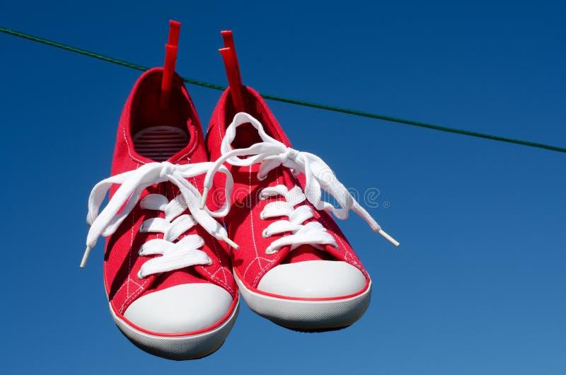 Neue rote Turnschuhe auf waschender Zeile lizenzfreies stockbild