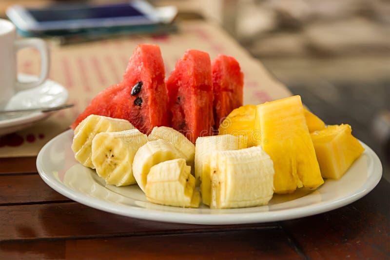 Neue saftige helle Frühstücksscheiben von Wassermelonenbananenananas auf einem weißen keramischen Teller, der Café im Freien flie lizenzfreie stockfotografie