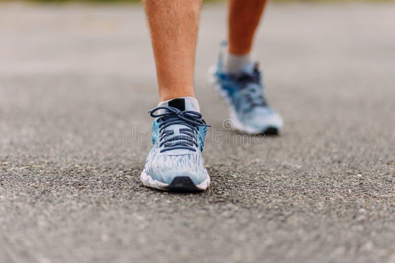 Neue saubere Laufschuhe auf den Füßen der Männer auf der Pflasterung im Sommer lizenzfreies stockfoto